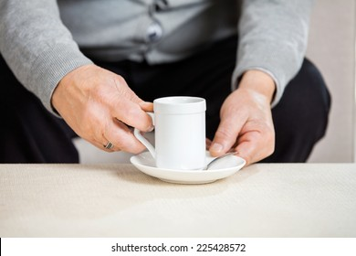 Midsection of senior man holding coffee cup on table at nursing home
