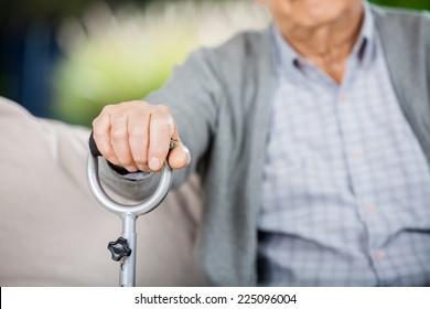 Midsection of senior man holding metal walking stick at nursing home