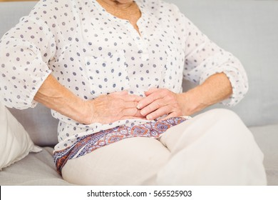 Midsection of senior woman suffering from stomach pain at home