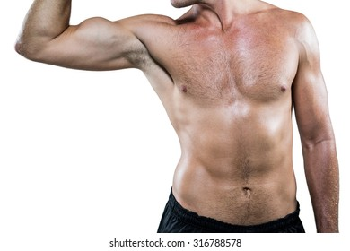 Midsection of shirtless athlete flexing muscles against white background