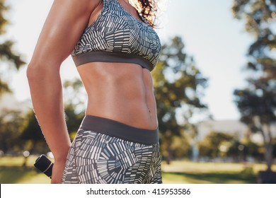 Midsection shot of fit woman in sportswear outdoors at the park. Very fit body with strong six-pack abs.