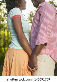 Midsection side view of an African American couple in garden holding hands