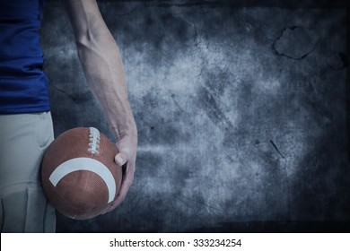 Midsection of sports player holding ball against dark background