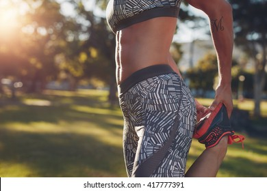 Midsection of sporty woman stretching her leg in park. Closeup shot of fitness female in sportswear exercising outdoors.