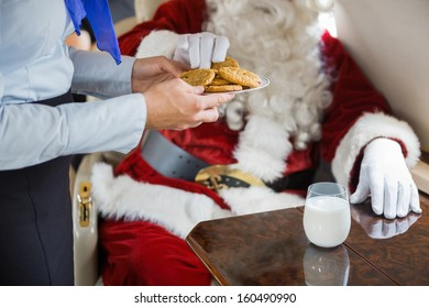 Midsection of stewardess serving cookies to Santa in private jet