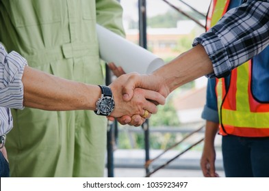 midsection of team of engineer and technician contractor shaking hands after finishing up business meeting to greeting start up project contract in construction site, partnership, teamwork concept