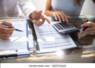 Mid-section Of Two Worker Calculating Report While Working Together In Office