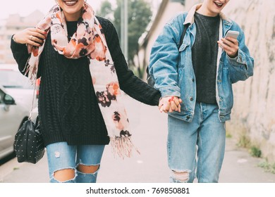 Midsection of two young women walking hand in hand - happiness, best friends, having fun concept