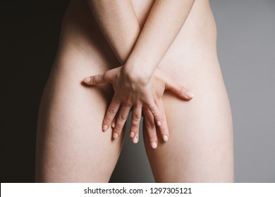 midsection of unrecognizable young naked woman covering her private parts or genital area with both hands - female sexuality or women's health concept