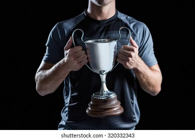 Midsection of victorious rugby player holding trophy against black background