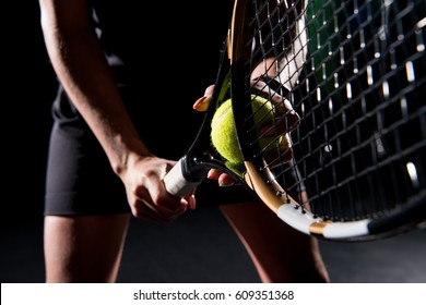 Midsection view of young woman holding tennis racket and ball isolated  on black