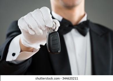 Midsection of waiter holding car key against gray background