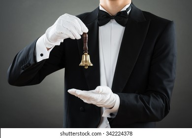 Midsection of waiter holding ring bell while standing against gray background