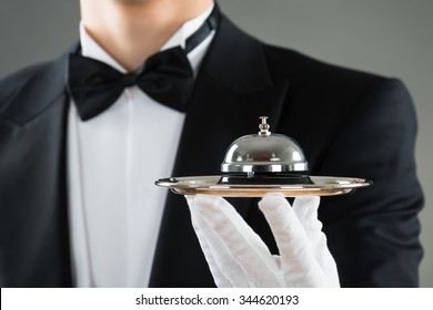 Midsection of waiter holding service bell in plate against gray background