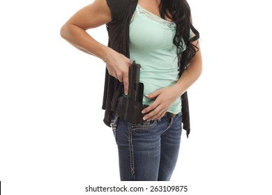 Midsection of woman drawing handgun from holster