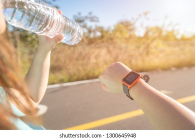 Midsection Of Woman Drinking Water On Road During Sunny Day