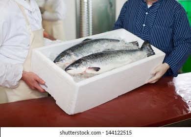 Midsection of workers carrying fish container at table