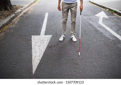 Midsection of young blind man with white cane walking on street in city.