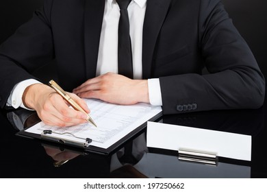 Midsection of young businessman writing on document at desk against black background