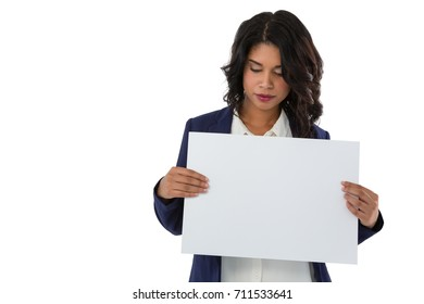 Midsection of young businesswoman holding blank placard against white background
