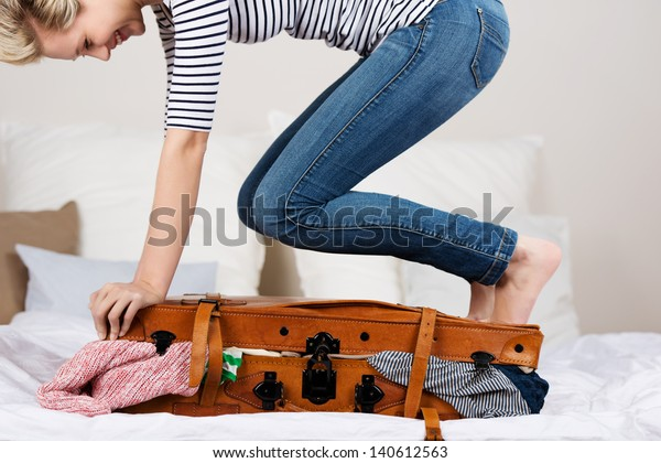 Midsection of young smiling woman packing suitcase on bed