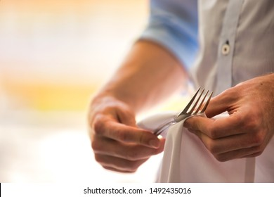 Midsection of young waiter cleaning fork in restaurant