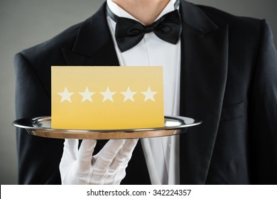 Midsection of young waiter holding tray with star rating label against gray background