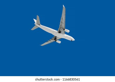 midsize long haul widebody white passenger airplane on a blue sky background bottom view a few seconds before landing composition photography flying overhead towards destination airport travel concept