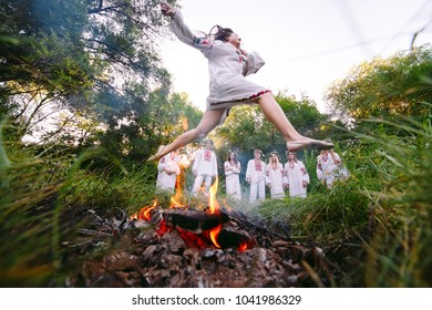 Midsummer. Girl jumping over the fire.