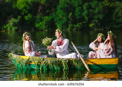 Midsummer. A group of young people in national costumes sail in a boat that is decorated with leaves and growths. Slavonic holiday of Ivan Kupala.