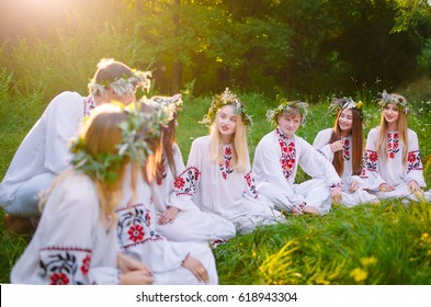 Midsummer. Group of young people of Slavic appearance are sitting around a campfire.