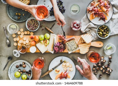 Mid-summer picnic with wine and snacks. Flat-lay of charcuterie and cheese board, rose wine, nuts, olives and peoples hands holding wineglasses and celebrating over concrete table background, top view