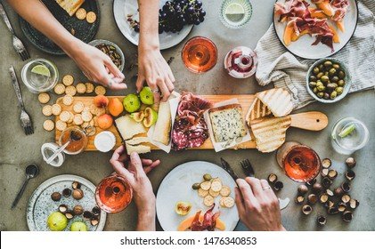 Mid-summer picnic with wine and snacks. Flat-lay of charcuterie and cheese board, rose wine, nuts, olives and peoples hands over concrete table background, top view. Family, friends holiday gathering