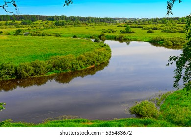 Midsummer rural landscape with field, river and blue sky