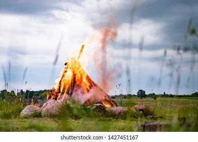 Midsummer solstice festive bonfire in field of grass