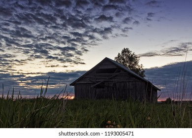 The midsummer sun barely sets behind the old barn house on the fields of the rural Finland. The sky is colored dramatically on this summer night.