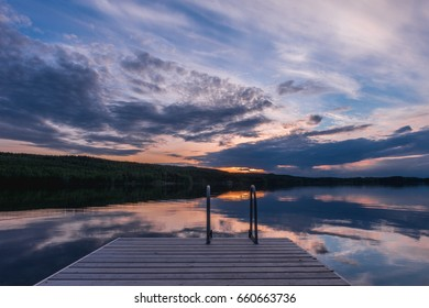 Midsummer sunset lake landscape. Scandinavian lake in the sunset with a long jetty. Finland. Europe travel.