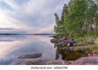 Midsummer sunset lake landscape. Scandinavian lake. Finland. Europe travel.