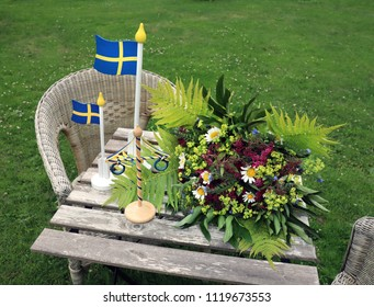 Midsummer in Sweden. Making a Summer bouquet (Spirea, daisy, fern, mantle). Swedish flagg and maypole decoration.