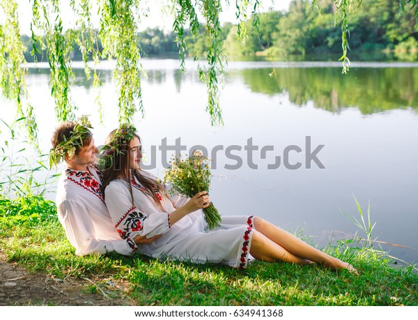 Midsummer. Young loving couple in Slavic costumes on the shore of the lake. Slavonic holiday of Ivan Kupala.