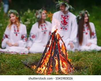 Midsummer. Young people in Slavic clothes sitting in the woods near the fire.