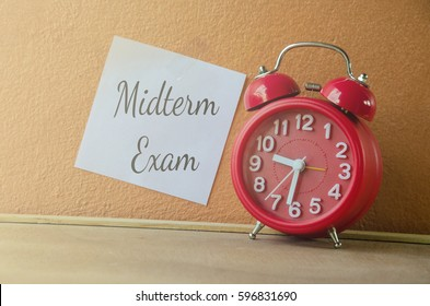Midterm Exam prepared week Midterm Exam text on paper memo at orange wall with red clock