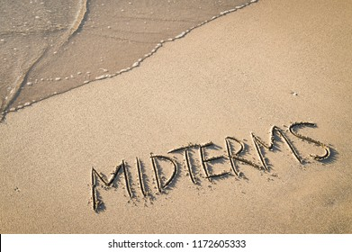 'MIDTERMS' written in the sand on the beach with the sea washing up the shore.