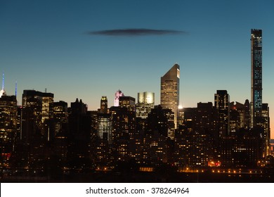 Midtown Manhattan cityscape with clear sky and one dark flat cloud during twilight in New York City.