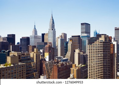 The Midtown Manhattan New York City Skyline as seen from a high rise building. Empire State Building, Chrysler Building and Met Life buildings are predominantly visible.