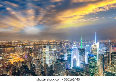 Midtown Manhattan skyscrapers night lights, aerial view of New York City.