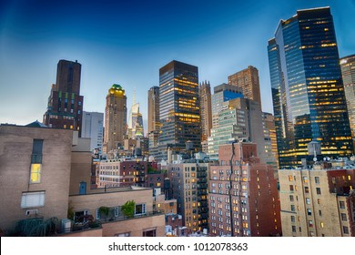 Midtown Manhattan skyscrapers as seen from city rooftop at sunset.