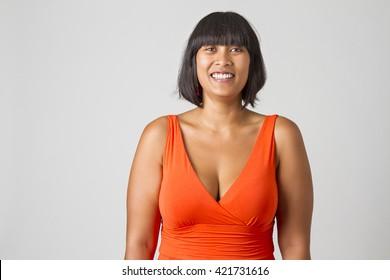 Mid-twenties filipino woman in low cut orange dress