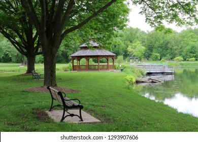 Midwest nature background with city park view.Beautiful late spring landscape with bench in a foreground, trees around the pond and wooden gazebo in a city park.Lakeview park, Middleton, Madison area.