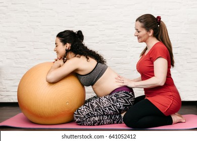 Midwife massaging a pregnant woman while exercising with a fitness ball